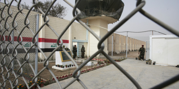 Guards stand at the entrance of a renovated Abu Ghraib prison, now renamed Baghdad Central Prison in Baghdad, Iraq, Saturday, Feb. 21, 2009. Iraq has reopened the notorious Abu Ghraib prison west of Baghdad, but it has a new name and officials promise more humane treatment of prisoners. The compound has come to symbolize American abuses after photos released in 2004 showed U.S. soldiers sexually humiliating inmates there.(AP Photo/Karim Kadim)