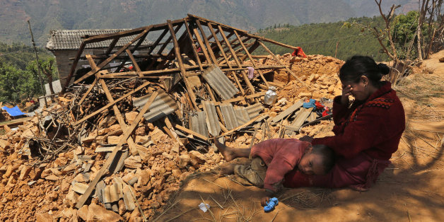 A Nepalese woman sits with her son near their house, destroyed in last week's earthquake, in Pauwathok village, Sindhupalchok district, Nepal, Saturday, May 2, 2015. Life has been slowly returning to normal in Kathmandu, but to the east, angry villagers in parts of the Sindhupalchok district said Saturday they were still waiting for aid to reach them. In the village of Pauwathok, where all but a handful of the 85 houses were destroyed, three trucks apparently carrying aid supplies roared by with