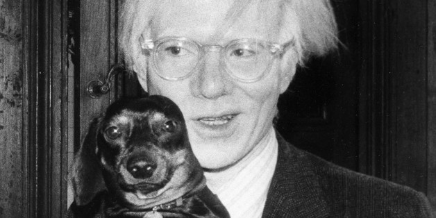 Pop artist Andy Warhol poses with a small dog in 1974. (AP Photo)