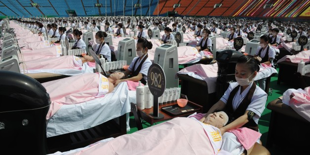 Beauticians apply facial care to women as they lay on beds in a stadium in Jinan, east China's Shandong province on May 4, 2015. A total of 1000 beauticians applied facial care to 1000 women at the same time in the open air to break a Guinness World Record, local media reported.    CHINA OUT   AFP PHOTO        (Photo credit should read STR/AFP/Getty Images)