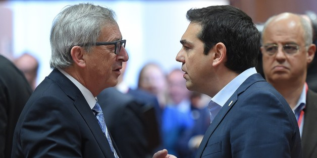 European Commission President Jean-Claude Juncker (L) speaks with Greek Prime Minister Alexis Tsipras as they take part in an emergency meeting to discuss Europe's response to the Mediterranean migrants crisis at the European Council in Brussels, April 23, 2015. AFP PHOTO/EMMANUEL DUNAND        (Photo credit should read EMMANUEL DUNAND/AFP/Getty Images)