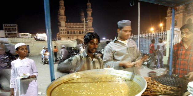 HYDERABAD, INDIA:  An Indian vendor prepares kebabs and non-vegetarian delicacies in his stall outside the Mecca mosque with the Char Minar in the background in Hyderabad, 20 October 2005.  Indians, like many millions of Muslims around the world, are observing the holy month of Ramadan -- a month of fasting and spiritual purity during which they refrain from eating, drinking or sex from dawn until dusk.  AFP PHOTO/Prakash SINGH  (Photo credit should read PRAKASH SINGH/AFP/Getty Images)