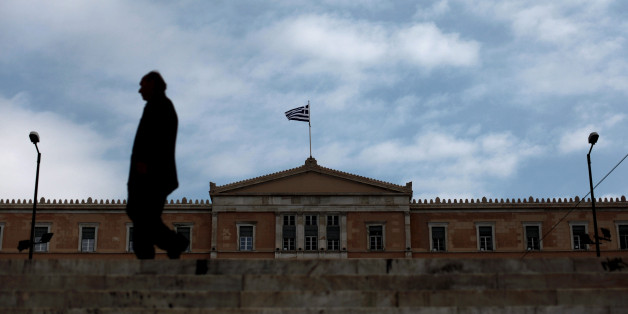 A man walks in front of the Greek Parliament in Athens on November 27, 2012. The eurozone and IMF saved Greece with a re-drawn rescue to avert bankruptcy and to cut the debt mountain on Tuesday which Greek leaders said marked a new beginning for their people facing yet further austerity in the midst of recession. AFP PHOTO / Angelos Tzortzinis        (Photo credit should read ANGELOS TZORTZINIS/AFP/Getty Images)