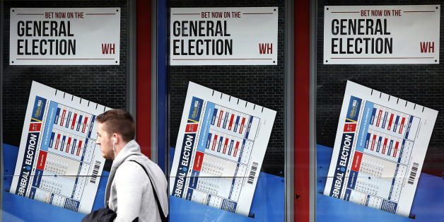 A member of the public walks past a betting shop window with a display for the General Election in Govan, Scotland, Wednesday, May 6, 2015. Britain goes to the polls in a General Election Thursday. (AP Photo/Scott Heppell)