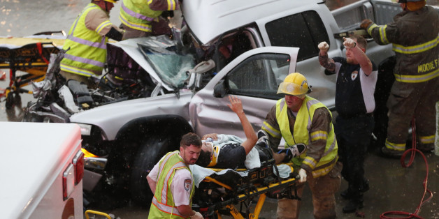 The driver of a truck which crashed during severe weather on Interstate 35 gestures to his rescuers after being cut from the truck in Moore, Okla., Wednesday, May 6, 2015. Forecasters declared a tornado emergency for Moore. (AP Photo/Sue Ogrocki)