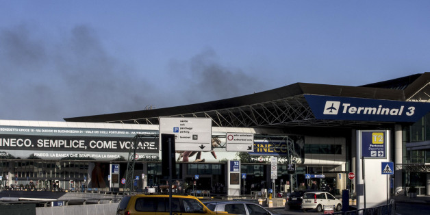 Smoke billows from Rome's Fiumicino airport main international terminal after a fire broke out overnight, Thursday, May 7, 2015. Italy's flagship Alitalia airline said in a statement that all departures have been canceled up to 2 p.m. (1200 GMT) and that only intercontinental flights will be allowed to land during that period.  The fire, which broke out after midnight, involved about 400 square meters (more than 4,000 square feet) of retail space. No cause was immediately identified. (Massimo Pe