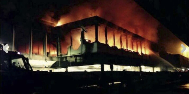 Flames rise from Rome's Fiumicino airport main international terminal after a fire broke out overnight, Thursday, May 7, 2015. Italy's flagship Alitalia airline said in a statement that all departures have been canceled up to 2 p.m. (1200 GMT) and that only intercontinental flights will be allowed to land during that period.  The fire, which broke out after midnight, involved about 400 square meters (more than 4,000 square feet) of retail space. No cause was immediately identified. (Domenico Pal