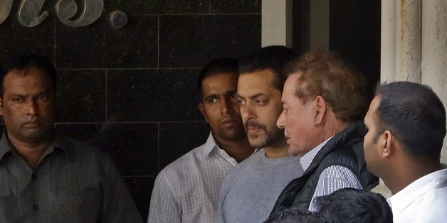 Bollywood actor Salman Khan, center, and his father Salim Khan, second right, come out of their residence to see off a guest in Mumbai, India, Thursday, May 7, 2015. One of India's biggest and most popular movie stars, Khan, was sentenced to five years in jail Wednesday on charges of driving a vehicle over five men sleeping on a sidewalk and killing one in a hit-and-run case that has dragged for more than 12 years. (AP Photo/Rajanish Kakade)