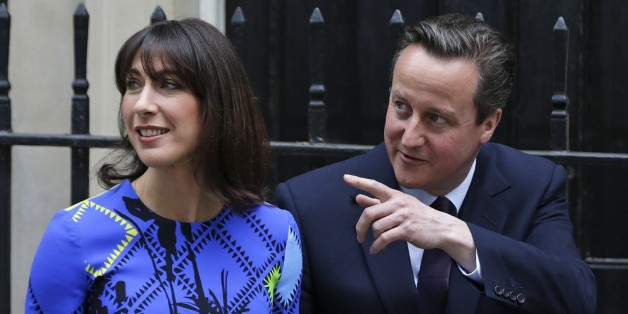 Britain's Prime Minister David Cameron gestures as he walks with his wife Samantha in Downing Street in London Friday, May 8, 2015. Cameron's Conservative Party swept to power Friday in Britain's Parliamentary elections winning an unexpected majority. (AP Photo/Alastair Grant )