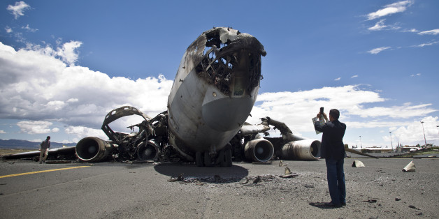 An airport official uses his mobile to take pictures of the wreckage of a military transport aircraft destroyed by Saudi-led airstrikes, at the Sanaa International airport, in Yemen, Tuesday, May 5, 2015. A Saudi-led coalition continues to bomb Shiite rebels also known as Houthis and allied forces across the country. The airstrikes campaign, which began on March 26, and the ground fighting have killed hundreds and displaced at least 300,000 Yemenis.  (AP Photo/Hani Mohammed)