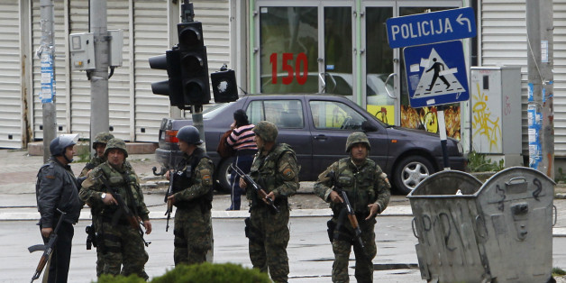 Police officers walk through a street near the scene of an altercation involving the police, in northern Macedonian town of Kumanovo, on Saturday, May 9, 2015. Authorities in Macedonia say police have clashed with an armed group in the northern town of Kumanovo, and parts of the town have been sealed off. (AP Photo/Boris Grdanoski)