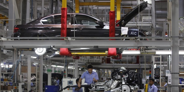 India's retired cricket star Sachin Tendulkar, center, fixes a gear shift to an engine as he assembles a BMW 5 Series at BMW's manufacturing facility on the outskirts of Chennai, India.