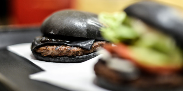 TOKYO, JAPAN - SEPTEMBER 18:  Black hamburgers are seen at a Burger King restaurant on September 18, 2014 in Tokyo, Japan. The black burgers, one a Kuro Pearl at 480 yen, has black buns and cheese smoked with bamboo charcoal and black sauce made of squid ink. The other, the Kuro Diamond at 690 yen, comes also with lettuce, tomato, onion and mayonnaise. The burgers are available from September 19 through early November in Burger King restaurants throughout Japan.  (Photo by Keith Tsuji/Getty Imag