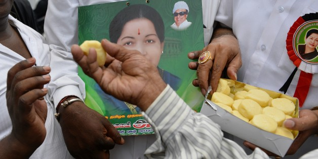 Supporters of All India Anna Dravida Munnetra Kazhagam (AIADMK) supremo, Jayalalithaa Jayaram distribute sweets as they hear the news of the acquital of their leader in the 18-year-old, disproportionate assets case in Bangalore on May 11, 2015.  The head of India's largest Tamil party was cleared of corruption May 11, 2015, a verdict that sparked wild celebrations by supporters and paved the way for the return of one of the country's most powerful politicians.     AFP PHOTO/ Manjunath KIRAN
