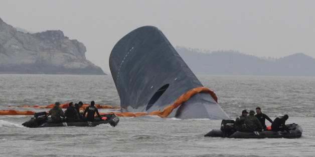 FILE - In this April 17, 2014 file photo, South Korean Coast Guard officers search for missing passengers aboard sunken ferry Sewol in the waters off the southern coast near Jindo, South Korea. One month after the ferry sinking that left more than 300 people dead or missing, there is a national debate - and spasms of shame and fury - over issues neglected as the country made its breakneck way from poverty, war and dictatorship to one of Asia's top economic, diplomatic and cultural powers. T