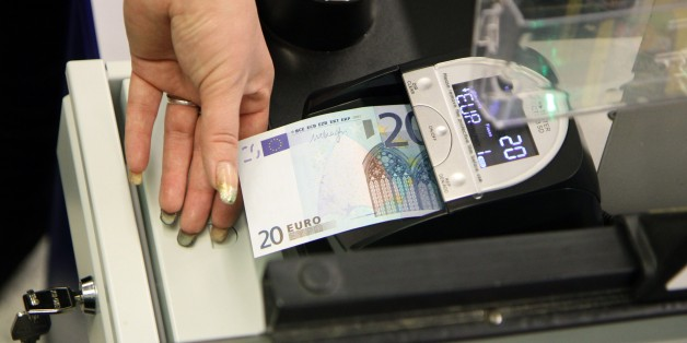 A cashier inspects a euro banknote  in a supermarket in Vilnius on January 1, 2015. Lithuania switched over to the euro on Thursday, becoming the last Baltic nation to adopt Europe's single currency in a bid to boost stability despite fears of inflation and eurozone debt woes. AFP PHOTO / PETRAS MALUKAS        (Photo credit should read PETRAS MALUKAS/AFP/Getty Images)