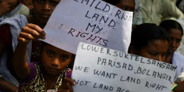 Indian protestors are joined by children holding placards during a rally in New Delhi on May 5, 2015, against the ruling governments proposed land acquisition bill.   Anger has also been mounting in rural Indian areas over  Prime Minister Narendra Modi's land reform bill, which the government says is needed speed up economic growth, but political opponents say favours big business at the expense of struggling farmers.   AFP PHOTO/MONEY SHARMA.        (Photo credit should read MONEY SHARMA/AFP/Ge
