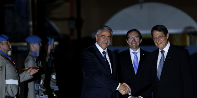 Cyprus' president Nicos Anastasiades, right, and Turkish Cypriot leader Mustafa Akinci shake hands as the United Nations envoy Espen Barth Eide, center, smiles before a dinner at the Ledra Palace Hotel inside the UN controlled buffer zone that divides the Cypriot capital Nicosia, on Monday, May 11, 2015. The dinner is the first meeting between Anastasiades and Akinci since the Turkish Cypriot politician _ a left-wing moderate _ soundly defeated the hard-line incumbent in an election last month.