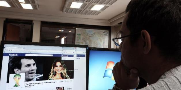 Un Iranien regarde une page Facebook contenant des informations concernant la star du football argentin Lionel Messi (g) et le mannequin brésilien Fernanda Lima, à son bureau à Téhéran, le 9 décembre 2013