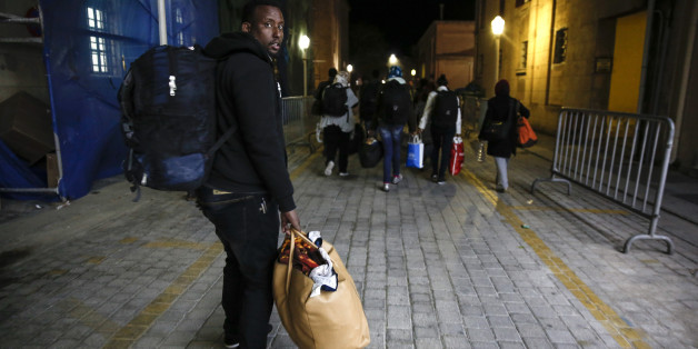 In this Wednesday, April 22, 2015 photo, migrants make their way to accommodate themselves after being processed by the Greek Coast Guard at the southeastern island of Rhodes.  Arrivals in Greece have more than doubled this year to exceed 10,000 _ including more than 1,000 in the past week alone _ as scores of people arrive daily on islands close to the Turkish coast. From there, they register with Greek authorities and then make their way by ferry to Athens, hoping to continue their clandestine