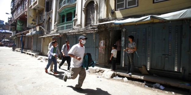 A Nepalese man runs to safety after a second earthquake hit Nepal in Kathmandu, Nepal, Tuesday, May 12, 2015.