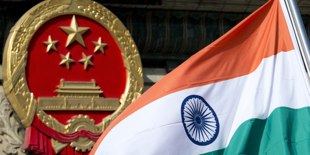 An Indian national flag is flown next to the Chinese national emblem during a welcome ceremony for visiting Indian Prime Minister Manmohan Singh, outside the Great Hall of the People in Beijing Wednesday, Oct. 23, 2013. China and India signed a confidence-building accord Wednesday to cooperate on border defense following a standoff between armed forces of the two Asian giants in disputed Himalayan territory earlier this year. (AP Photo/Andy Wong)