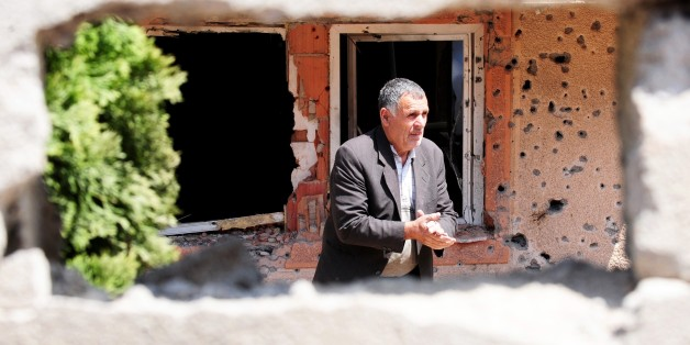 A man walks through a destroyed house in Kumanovo on May 12, 2015. Special police units pulled out of the northern Macedonian town early on May 11 where 22 people, including eight officers, were killed over the weekend in worst violence in the country since its 2001 inter-ethnic conflict. Thirty men were later charged with terror offences.  AFP PHOTO / ROBERT ATANASOVSKI        (Photo credit should read ROBERT ATANASOVSKI/AFP/Getty Images)