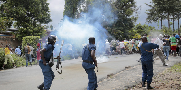Demonstrators trying to march to the town center flee as police disperse them with tear gas, in the Ngagara district of Bujumbura, Burundi Wednesday, May 13, 2015. A police officer opened fire at protesters in Burundi's capital Wednesday as demonstrations against the president's bid for a third term heated up, with troops surrounding the national radio station. (AP Photo/Gildas Ngingo)