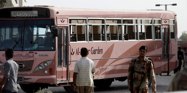 A Pakistani paramilitary trioop stands guard near a bus targeted by attackers in Karachi, Pakistan, Wednesday, May 13, 2015. Gunmen killed dozens of people on Wednesday aboard a bus in southern Pakistan bound for a Shiite community center, in the latest attack targeting the religious minority, police said. (AP Photo/Fareed Khan)