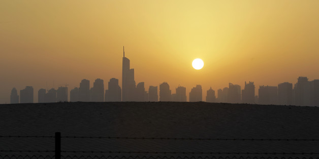 The sun sets behind the city skyline at the Marina district as the Almas tower is seen in Dubai, United Arab Emirates, Friday, March 7, 2014. (AP Photo/Kamran Jebreili)