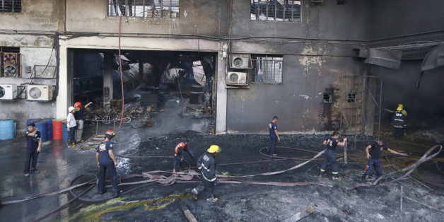 Firemen work to put the fire under control at a still-smoldering Kentex rubber slipper factory in Valenzuela city, a northern suburb of Manila, Philippines, Wednesday, May 13, 2015. A fire gutted the factory, possibly killing dozens of workers who ran to the second floor in hopes of escaping only to become trapped by inferno, officials said. Fire officials said there were no survivors found after the fire was put under control, said Mayor Rex Gatchalian of Valenzuela. (AP Photo/Bullit Marquez)