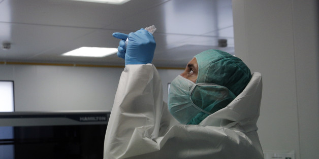 A forensic scientist of the Criminal Research Institute of the National Gendarmerie (IRCGN), collects DNA taken from the body parts of people involved in the crash of Germanwings jetliner, in Pontoise, outside Paris, France, Monday, March 30, 2015. The process of identifying the victims of Germanwings crash has now entered its active phase, but the families will still have to wait months to find out if their loved ones are among the bodies found. (AP Photo/Christophe Ena, Pool)