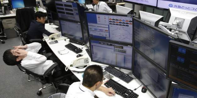 Money traders work at a computer terminal at a foreign exchange brokerage in Tokyo, Friday, Dec. 5, 2014. The dollar gained to 119.89 yen from 119.76 yen. The euro fell to $1.2384 from $1.2386. (AP Photo/Shizuo Kambayashi)