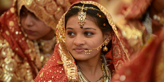 An Indian Muslim bride gestures during a mass wedding ceremony at the ancient Sarkhej Roja in Ahmedabad on February 22, 2013.  Some 151 couples participated in a mass marriage organised by Hussaini Waqaf Committee. Participation in mass marriages in the Muslim and Hindu communities are on the rise against the 'Dowry System' in which huge donations are paid by the bride's family members to the family members of the grooms. Instead, in the mass marriages the brides are gifted with the basic necesi
