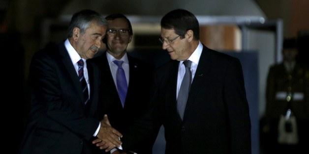 Cyprus' president Nicos Anastasiades, right, shakes hands with Turkish Cypriot leader Mustafa Akinci as the United Nations envoy Espen Barth Eide, center, looks on before a dinner at the Ledra Palace Hotel inside the UN controlled buffer zone that divides the Cypriot capital Nicosia, on Monday, May 11, 2015. The dinner is the first meeting between Anastasiades and Akinci since the Turkish Cypriot politician _ a left-wing moderate _ soundly defeated the hard-line incumbent in an election last month. Cyprus was split in 1974 when Turkey invaded after a coup by supporters of union with Greece. (AP Photo/Petros Karadjias)