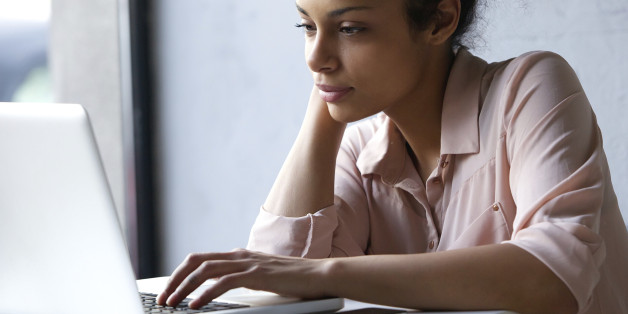 Close up portrait of a young black woman looking at laptop
