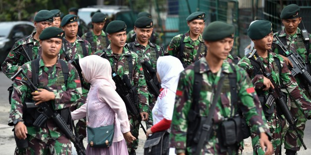 Indonesian women walk past soldiers providing security in Bandung on western Java island on April 23, 2015, ahead of a planned walk by participating heads of states scheduled for April 24 for the 60th Asian-African Conference. Asian and African leaders have gathered in Indonesia this week to mark 60 years since a landmark conference that helped forge a common identity among emerging states, but analysts say big-power rivalries will overshadow proclamations of solidarity. AFP PHOTO / Bay ISMOYO