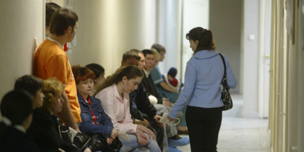 People sit in a hallway at the Saratov regional AIDS center, waiting for blood tests and other medical work in Saratov, 700 kilometers (450 miles) southeast of Moscow, Thursday, May 11, 2006. The country faces a widening epidemic as HIV/AIDS spreads beyond drug users, gay men and prostitutes, into the larger population. (AP Photo/Mikhail Metzel)