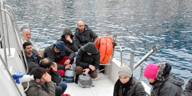 In this Sunday, Jan. 19, 2014 photo  immigrants believed to be Syrians sit on a Greek Coast Guard vessel after being detained by Greek authorities in the southeastern island of Symi. In another incident near the eastern Aegean sea near Farmakonissi islet on Monday, Jan. 20, 2014, Greek rescuers are seeking 12 people reported missing after a fishing boat packed with immigrants that was being towed to the shore by a coastguard vessel capsized in the dark. A Merchant Marine Ministry statement says another 16 people were rescued and their nationalities were unknown. (AP Photo/Nikolas Nanev)