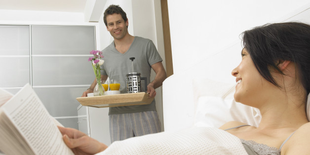 Man bringing 'breakfast in bed' to woman, smiling