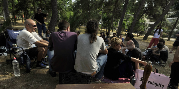 TO GO WITH AFP STORY by Roland Lloyd Parry:   Patricipants of a time-exchange network stage a  pic-nic for new members at an Athens park on May 27, 2012 to indroduce  an online exchange where members swap services, counting the cost not in euros, but in hours. More than 1,000 people are registered on the Athens time bank, of which around 200 active members regularly use it to give and receive services. Time-banking and other forms of bartering are on the rise in Greece and other crisis-hit countries such as Spain, as people come to grips with lower salaries, pensions and job prospects.  AFP PHOTO/ LOUISA GOULIAMAKI        (Photo credit should read LOUISA GOULIAMAKI/AFP/GettyImages)