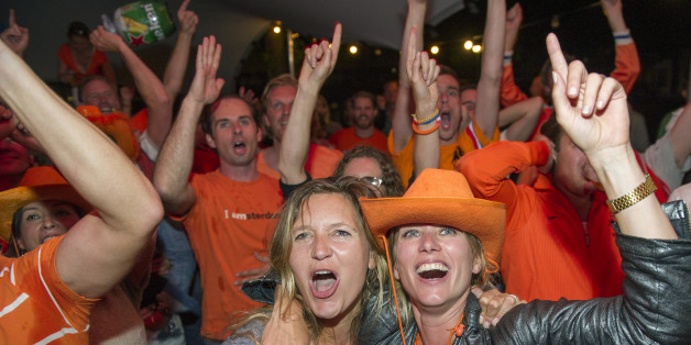 People celebrate as they watch the Dutch team win after penalties in the World Cup quarter finals soccer match between the Netherlands and Costa Rica at Strandzuid in Amsterdam, Saturday, July 5, 2014. (AP Photo/Patrick Post)