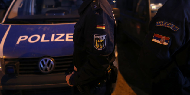 A member of the German border police, center, passes by his vehicle while monitoring a stretch of the Serbian border with Hungary in the village of Hajdukovo, some 180 kilometers north of Belgrade, Serbia, Friday, Feb. 13, 2015. Some 20 German police officers, equipped with vehicles with thermal vision cameras, joined Serbian security forces on Serbia's border with Hungary on Friday to try to halt a torrent of migrants that has alarmed many European Union countries. (AP Photo/Darko Vojinovic)