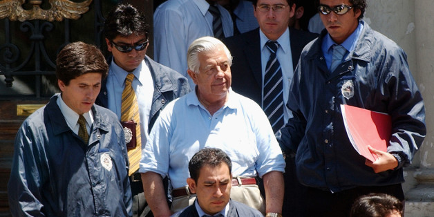 FILE - In this Jan. 28, 2005 file photo, retired Gen. Manuel Contreras, center, who headed the security service under former dictator Gen. Augusto Pinochet, leaves police headquarters in Santiago, Chile. The former chief of the feared spy agency responsible for kidnapping, torturing and killing thousands during Chile's military dictatorship accumulated 500 years in prison sentences on May 20, 2015. The 86-year-old has been serving a combined sentence for crimes against humanity. (AP Photo, File) CHILE OUT - NO USAR EN CHILE