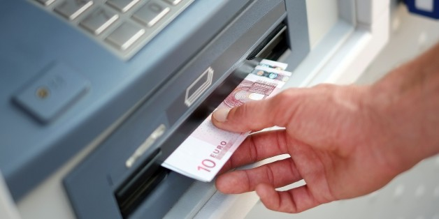A man takes out Euro banknotes from an automated teller machine (ATM) at a cash point of the French bank 'La Banque Postale' in Carquefou, Western France, on September 10, 2014.  AFP PHOTO / JEAN-SEBASTIEN EVRARD        (Photo credit should read JEAN-SEBASTIEN EVRARD/AFP/Getty Images)