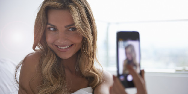 Stock image: Young woman taking selfie with cameraphone.