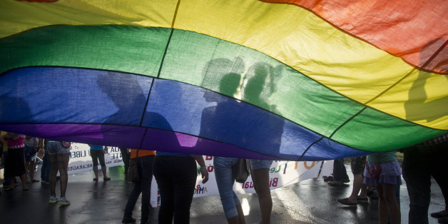 Members of the LGBT movement hold a gay pride flag as they attend a march to mark the International Day Against Homophobia in Managua, Nicaragua, Sunday, May 17, 2015. (AP Photo/Esteban Felix)