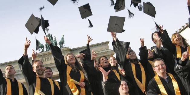 Graduates of the private 'International Business School Berlin' (IBS) throw their doctoral caps in the air as they pose for a family picture 31 January 2008 in front of the Brandenburg Gate in Berlin. The young men and women finished their studies in international management.    AFP PHOTO    DDP/MICHAEL KAPPELER    GERMANY OUT     (Photo credit should read MICHAEL KAPPELER/AFP/Getty Images)