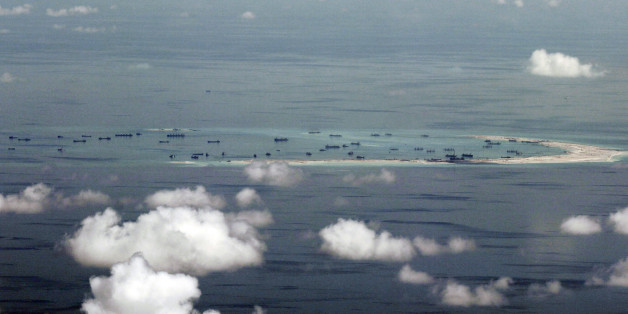 This areal photo taken through a glass window of a military plane shows China's alleged on-going reclamation of Mischief Reef in the Spratly Islands in the South China Sea Monday, May 11, 2015. Gen. Gregorio Pio Catapang, the Philippines' military chief, has flown to Pag-asa Island, a Filipino-occupied island in the South China Sea amid territorial disputes in the area with China, vowing to defend the islet and help the mayor develop tourism and marine resources there. (Ritchie B. Tongo/Pool Photo via AP)