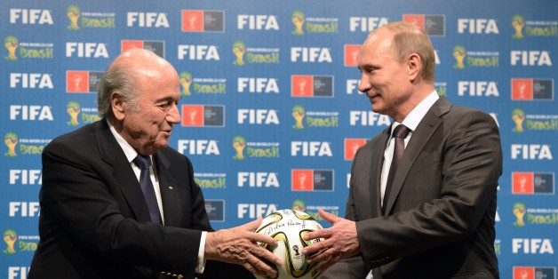 FILE - In this file photo taken on Sunday, July 13, 2014, FIFA President Sepp Blatter, left, and Russian President Vladimir Putin hold a soccer ball during the official ceremony of handover to Russia as the 2018 World Cup hosts, after the World Cup final soccer match between Germany and Argentina at the Maracana Stadium in Rio de Janeiro. Russian football is plagued by a racist and far-right extremist fan culture that threatens the safety of visitors to the 2018 World Cup, a dossier provided to The Associated Press revealed on Friday, Feb. 27, 2015. Researchers from the Moscow-based SOVA Center and the Fare network, which helps to prosecute racism cases for UEFA, cataloged more than 200 cases of discriminatory behavior linked to Russian football across two seasons.(AP Photo/RIA-Novosti, Alexei Nikolsky, Presidential Press Service, File)